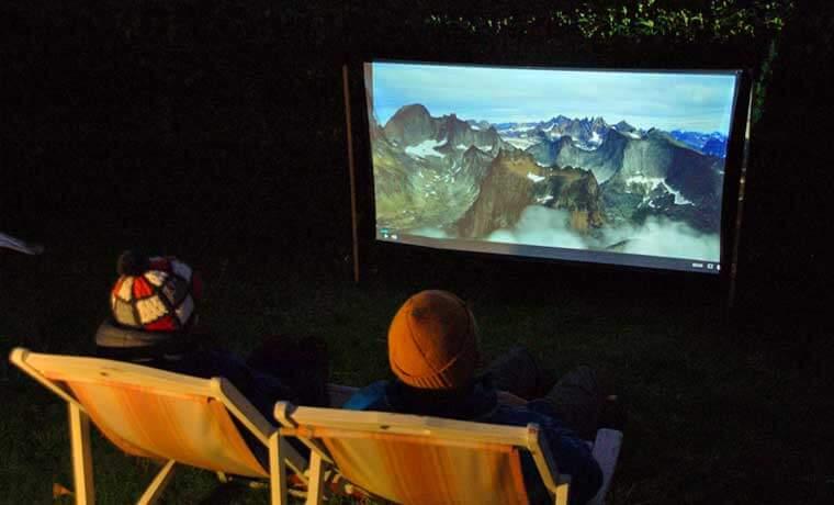 キャンプ場でプロジェクター映画を楽しむ様子
